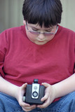 boy looking at old camera poster