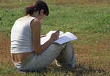 student girl reading notebook on a grass poster