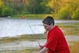 boy eating hotdog while fishing poster