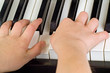 childs hands playing the piano