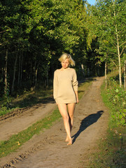 girl wolking along the forest roud