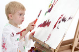 addorable toddler boy painting at easel poster