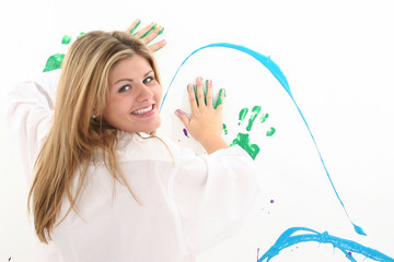 beautiful young woman painting on wall