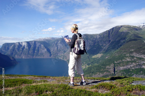 poster of active woman at the top of mountains over the lake