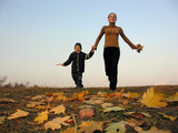 running mother with son on autumn leaves
