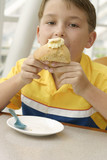 hungry appetite:  child eating a delicious baked muffin poster