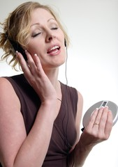blonde woman singing while listening to cd player