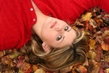 beautiful young woman laying in leaves poster