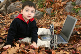 adorable boy in leaves with laptop poster