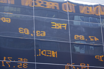 glass building reflecting neon ticker tape sign