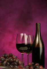 vertical of wine bottle with glasses and grapes