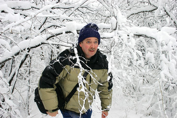man walking through snow filled branches