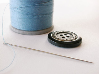 thread needle and button on white background