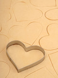 heart cookie cutter on a sheet of cookie dough poster