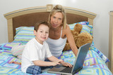 mother and son with laptop in bed poster