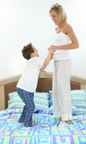 mother and son playing in bed poster