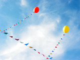 yellow and red balloons flying in blue sky poster