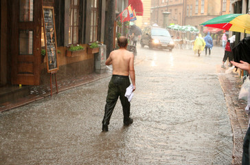 man without shirt walking in the rain