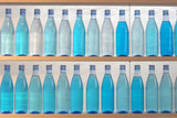 bottles filled with water, standing on the shelf poster