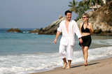 young couple walking on the beach poster