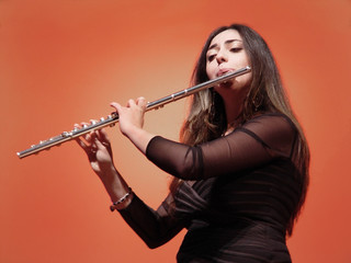 beautiful girl playing flute at the concert