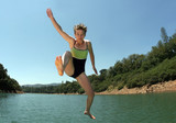 young woman jumping in the lake poster