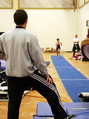 coach assisting a boy jumping on vault