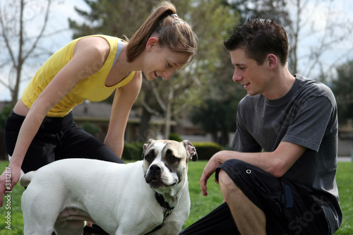 poster of teenagers playing with a dog in the park