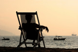 woman sitting in the chair watching sunset at the poster