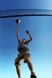 young man hitting the ball over the net poster