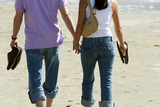 couple walking on the beach poster