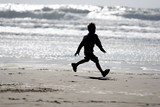 boy running on the beach poster