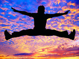 boy jumping high in the air against the sunset poster