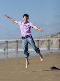boy jumping on the beach poster