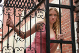 beautiful young woman looking through iron gate poster