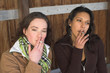 two girls smoking outside