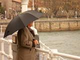 hombre con paraguas mirando al mar poster
