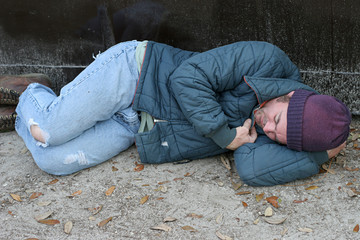 homeless man - asleep by dumpster