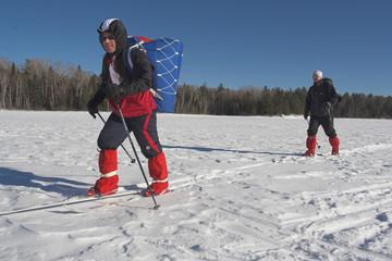 skiers traversing lake