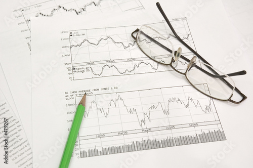 stock graphs, pencil and glasses