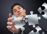 business man arranging puzzle poster
