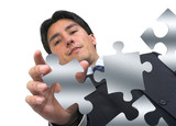 business man arranging puzzle on white poster