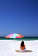 woman sitting on spanish beach under sun umbrella. white sand bl