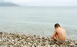 boy, sea and pebble poster