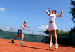 two female tennis players playing doubles in the sun. one is lea