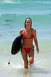 woman on sunny spanish beach in sea after surfing and body board