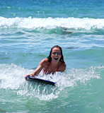 girl smiling while riding a big blue wave on a body board on the