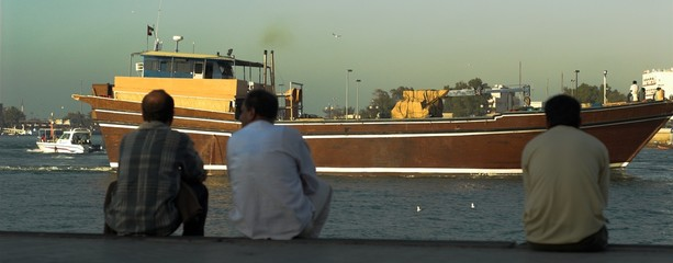 indian and pakistan workers watching boat in dubai