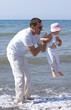 man lifting his daughter and playing in the sea