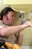 plumber using pipe wrench poster